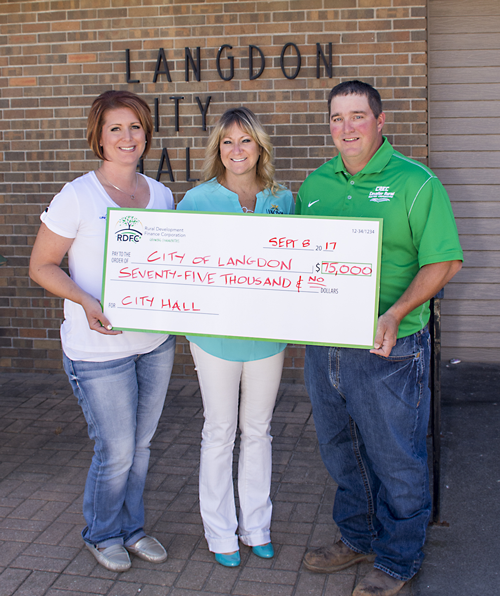Photo Caption: Kristen Gendron (left), United Communications, and Marty Tetrault (right), Cavalier Electric Cooperative, present a loan check to Langdon City Auditor Roxanne Hoffarth (center).